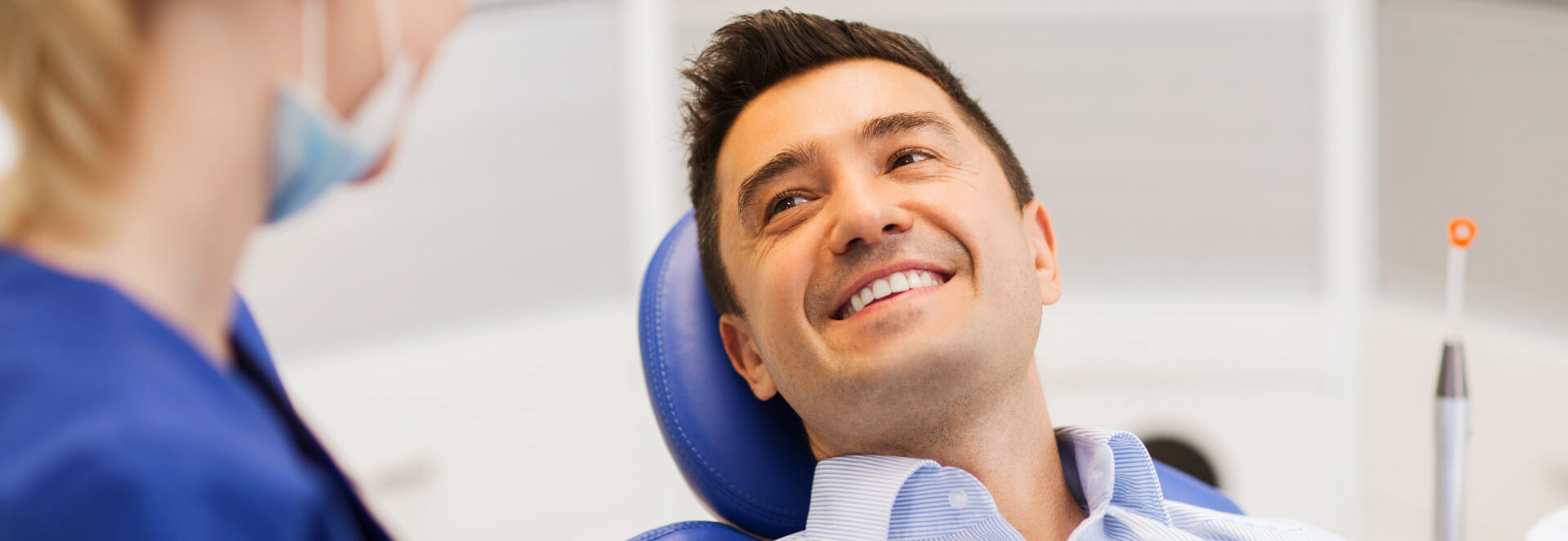 Male patient smiling with dental assistant