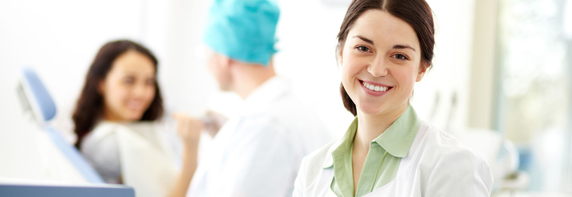 Dental assistant smiling at the camera while patient is receiving treatment