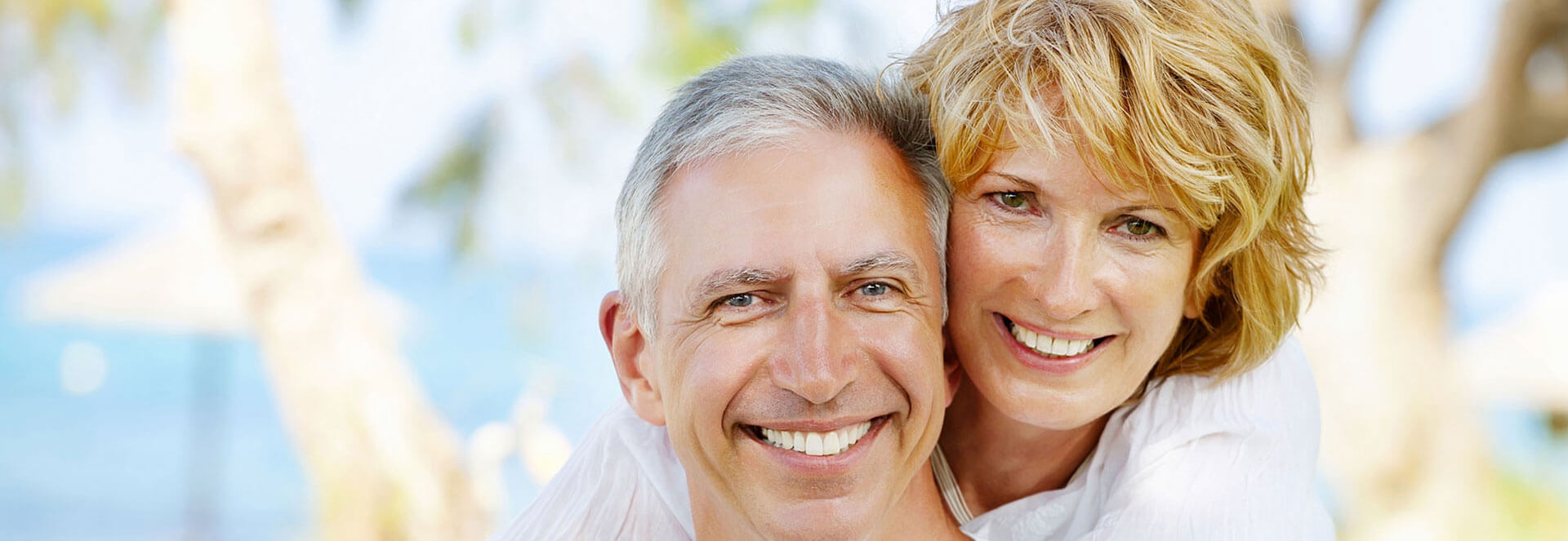 Elderly couple embracing each other smiling at the camera