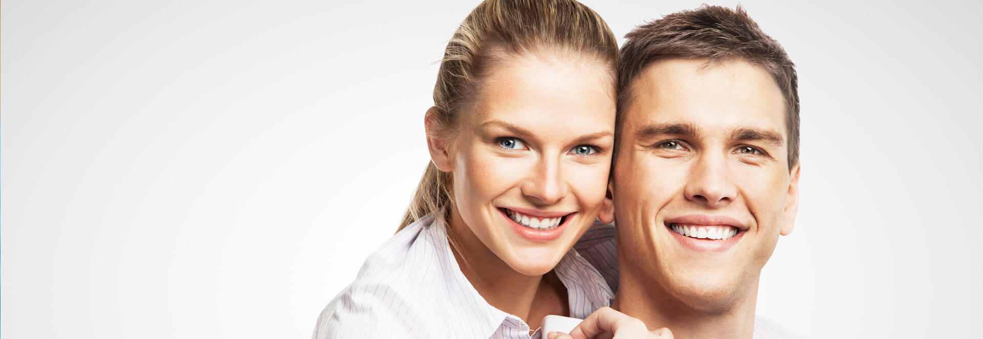 Young couple embracing each other and smiling at the camera