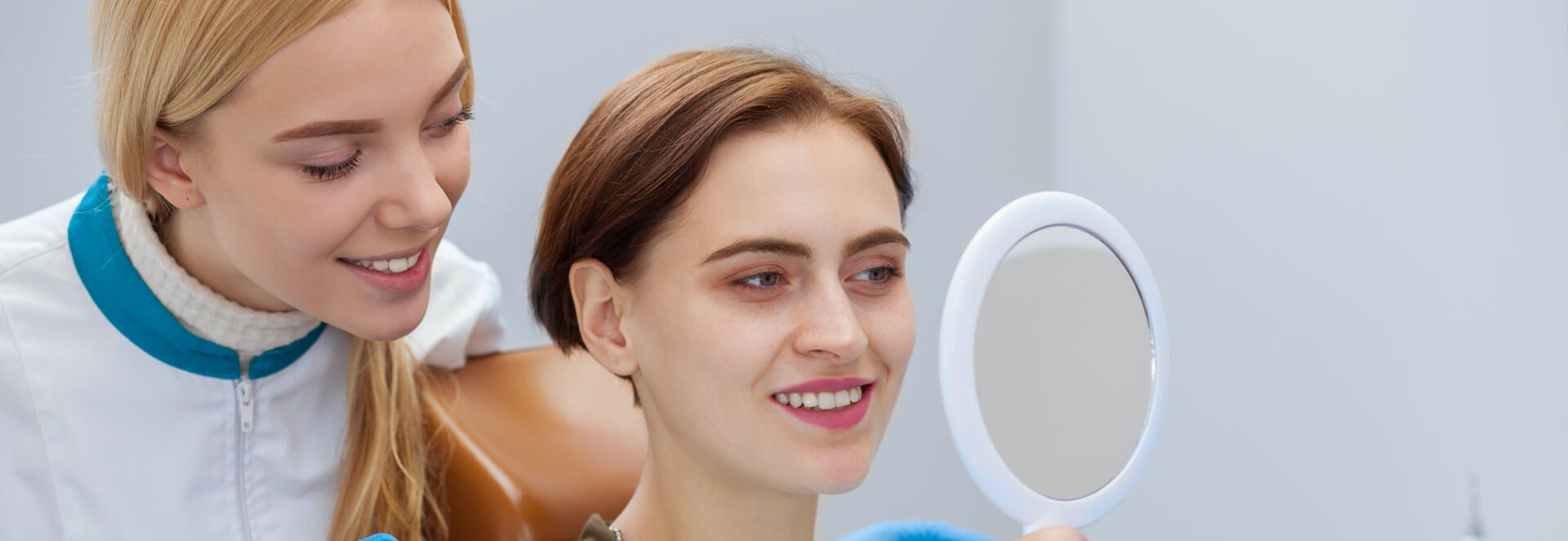 Female patient looking at her new dental crowns using a hand mirror while dental assistant is behind
