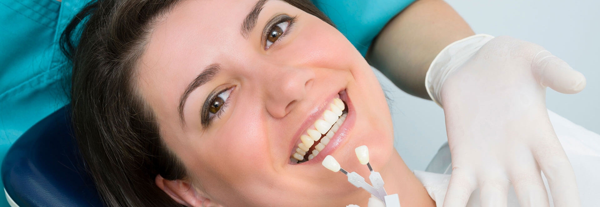 Comparing a pair of porcelain veneers with a smiling female patient