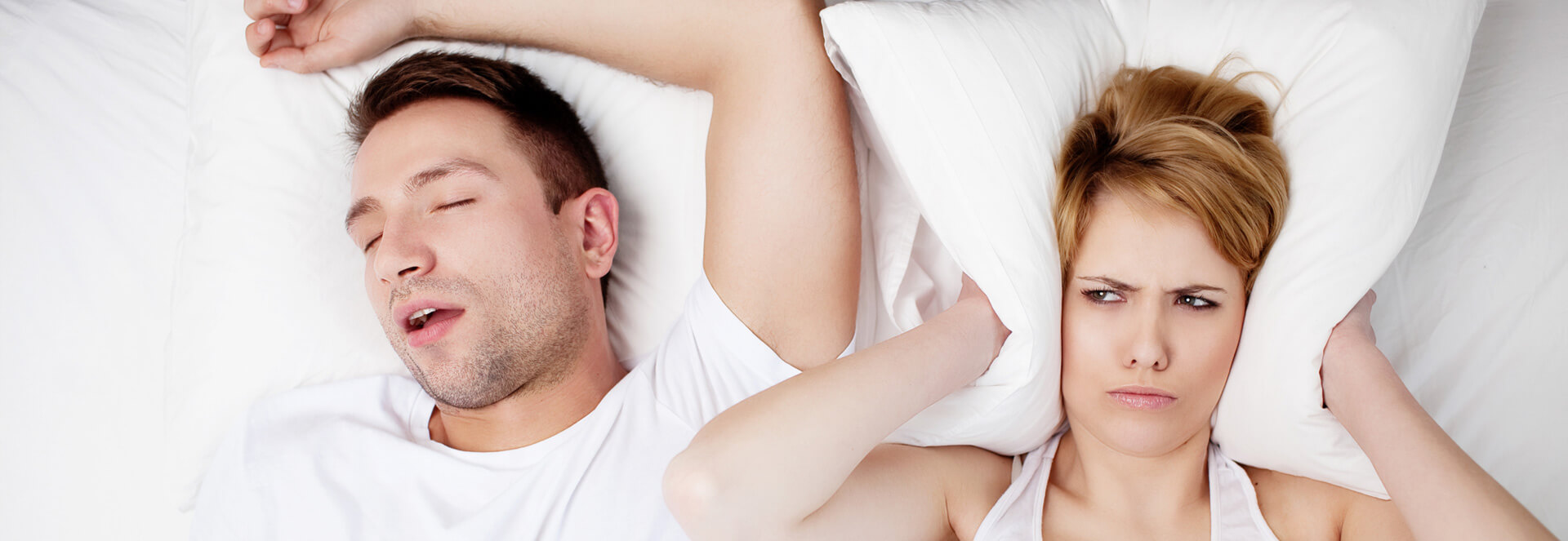 Unhappy female having a pillow covering her ears while male is snoring during sleep